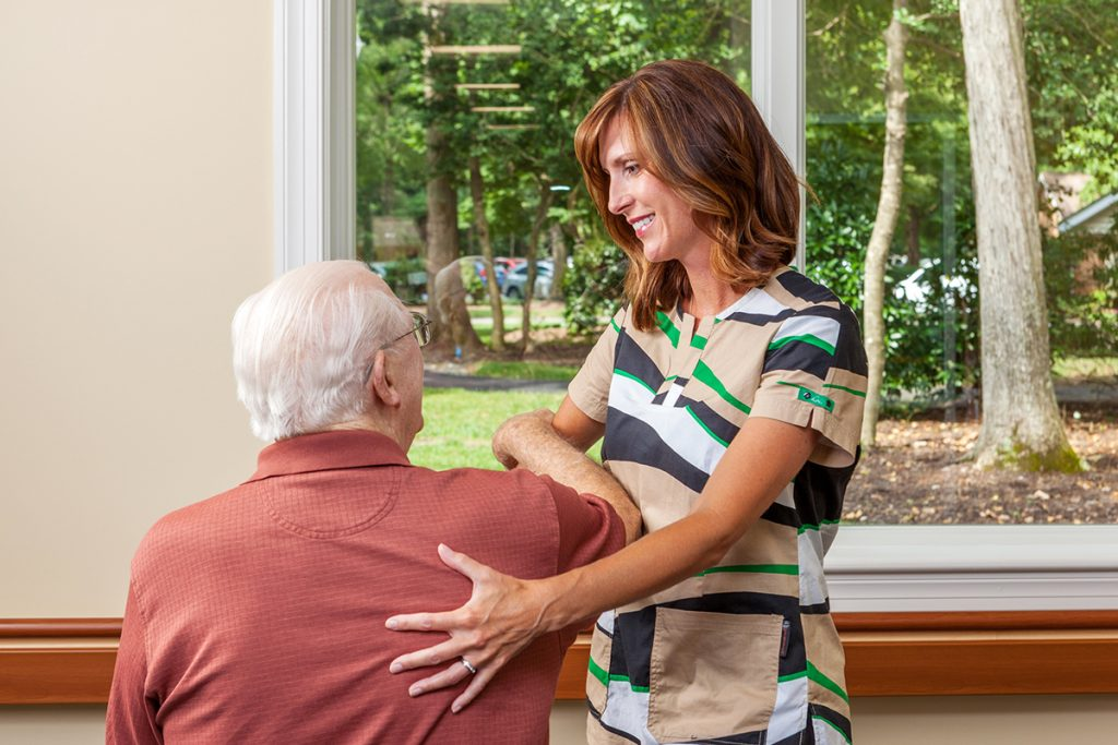 A personal care aide assists a patient with flexibility exercises