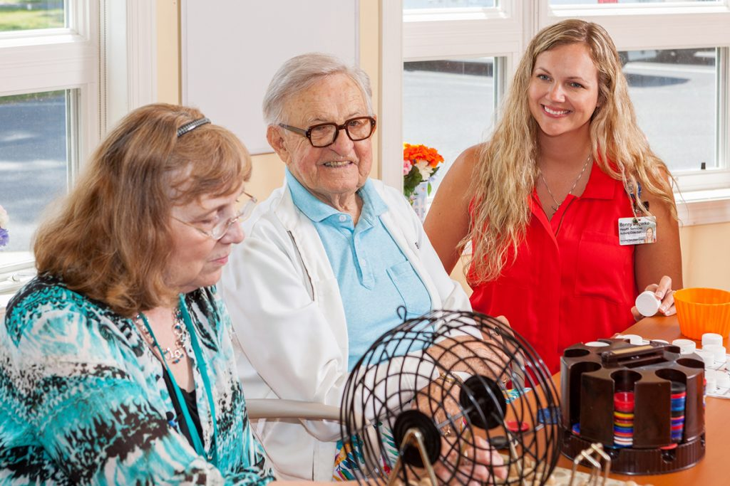 A personal care aide assists patients playing bingo