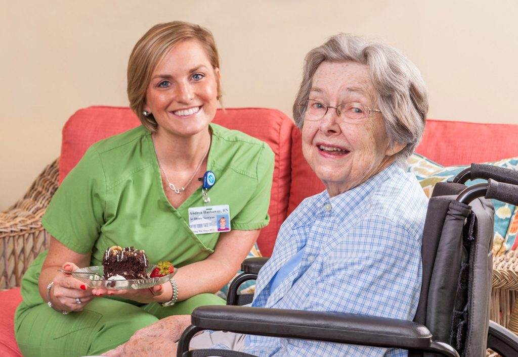A nurse assists a patient with eating some yummy cake